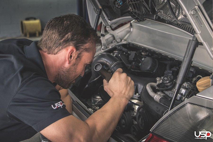 Chris Green, the owner of USP, under the hood of a customers Porsche